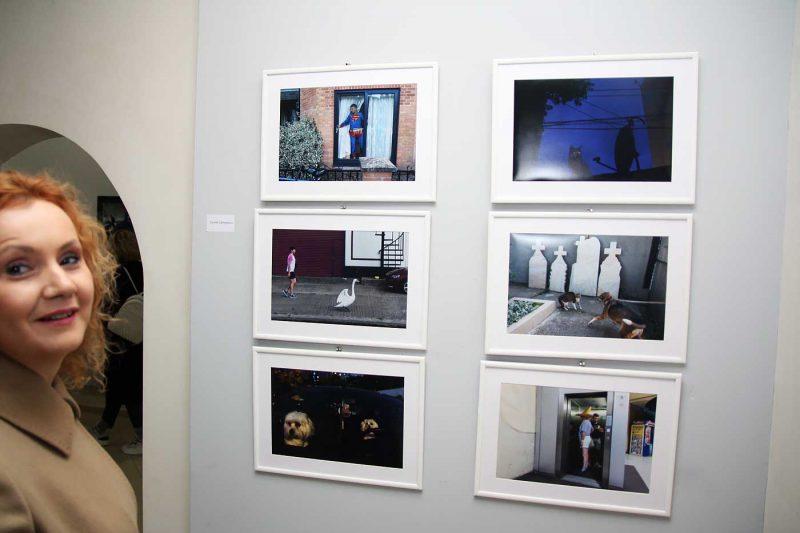 Vizitatori in expozitie. Pe perete, o parte dintre fotografiile lui Cosmin Garlesteanu © mondorama.ro