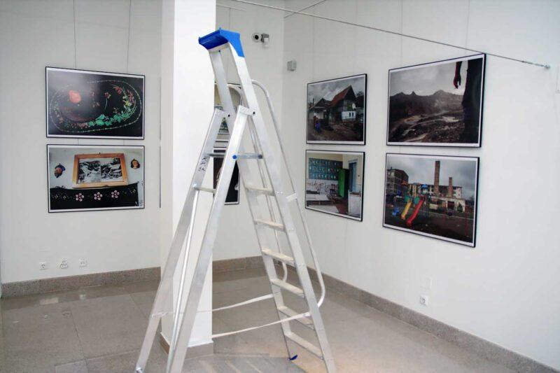 Pentru imaginile pe două rânduri s-a folosit o scară de aluminiu. Pe perete, fotografiile lui Bogdan Croitoru. © mondorama
