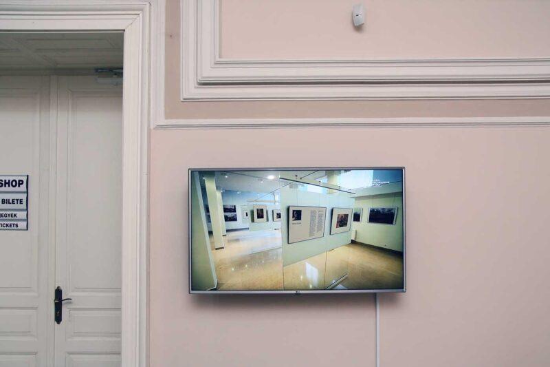 Pe televizorul din holul principal ruleaza un video de prezentare a expoziției. © mondorama