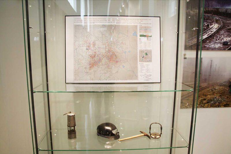 Una dintre cele două vitrine pregătite cu câteva piese de colecție pentru intrarea în atmosfera Roșiei Montane și o hartă a labirintului de galerii din zonă. © mondorama